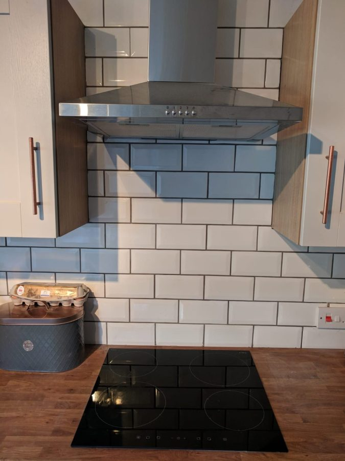 Feathering Your Nest How To Save Money In Your First Home by Fashion Du Jour LDN. White glazed brick subway tile, grey grout, grey kitchen, rose gold handle, wooden sideboard, induction hob, silver extractor hood