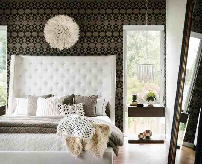 Sweet Dreams: Our 2020 Bedroom Interior Trend Predictions by Fashion Du Jour LDN. Close-up of monochrome tribal wallpaper, cream upholstered tufted bed, fur throws, black, cream, grey bedroom interior