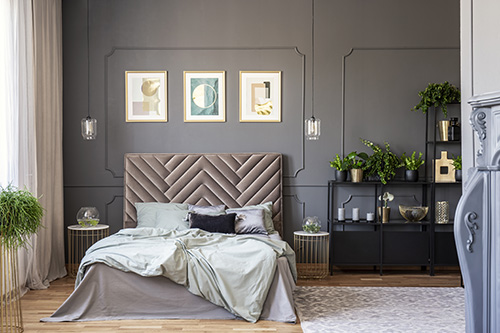 Sweet Dreams: Our 2020 Bedroom Interiors Trend Predictions by Fashion Du Jour LDN. Close-up of a velvet headrest, posters on the wall, pillows and glass lamps in a grey bedroom interior