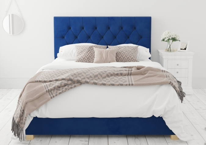 Sweet Dreams - 2020 Bedroom Interior Trend Predictions by Fashion Du Jour LDN. Close-up of a navy tufted upholstered headrest, pillows and white flowers in a white and grey bedroom interior