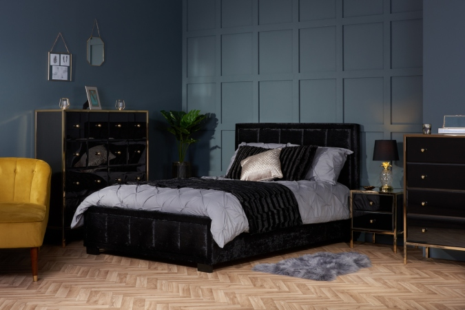 Sweet Dreams - 2020 Bedroom Interiors Trend Predictions by Fashion Du Jour LDN. Close-up of a black velvet bed, grey paneling on the walls,black and chrome gloss furniture, pillows and glass lamps in a grey bedroom interior
