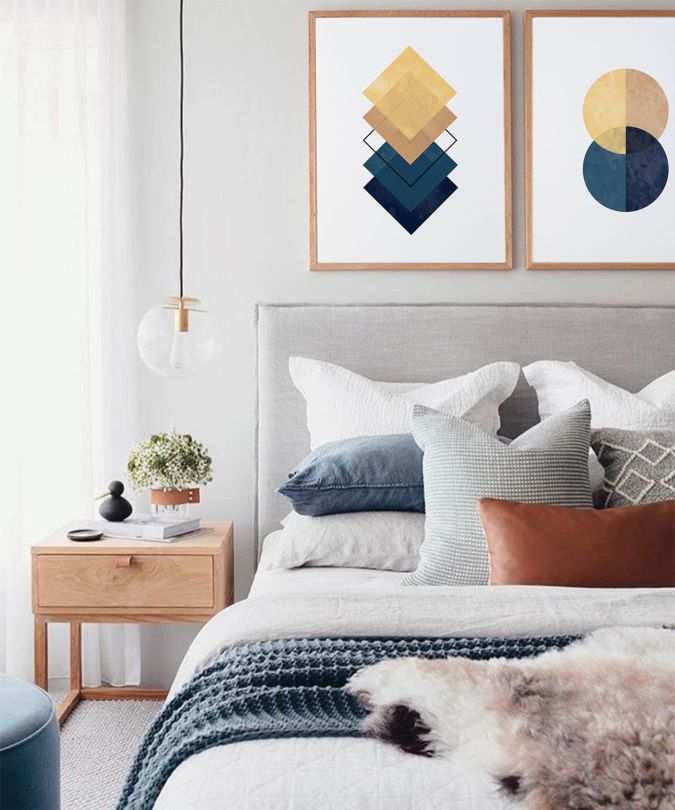 Sweet Dreams: Our 2020 Bedroom Interior Trend Predictions by Fashion Du Jour LDN. Close-up of abstract geometric wall art and a grey velvet upholstered bed frame, pillows in a variety of textures including knitted, wooden bedside table in a grey, white, navy, mustard and terracotta bedroom interior