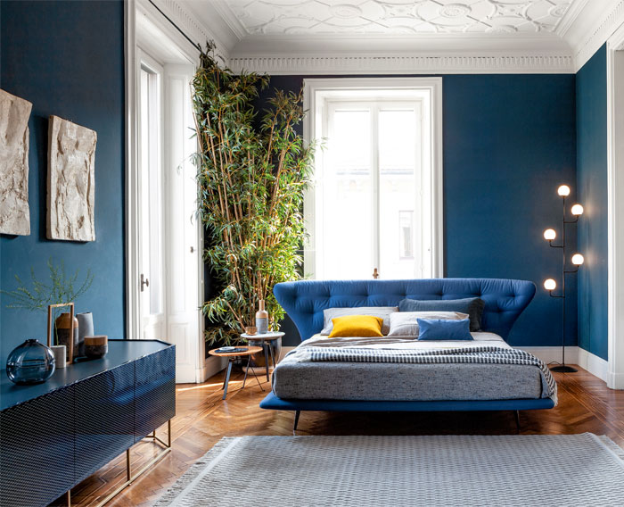 Sweet Dreams: Our 2020 Bedroom Interior Trend Predictions by Fashion Du Jour LDN. Close-up of teal painted wall, brushed chrome light fittings and lamps, blue upholstered bed, velvet cushions, navy, mustard and grey bedroom interior