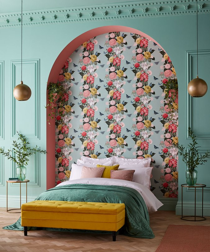 Sweet Dreams: Our 2020 Bedroom Interior Trend Predictions by Fashion Du Jour LDN. Close-up of bright floral Graham and Brown wallpaper, mint green wall paneling, mustard velvet ottoman, mint green, coral and mustard bedroom interior