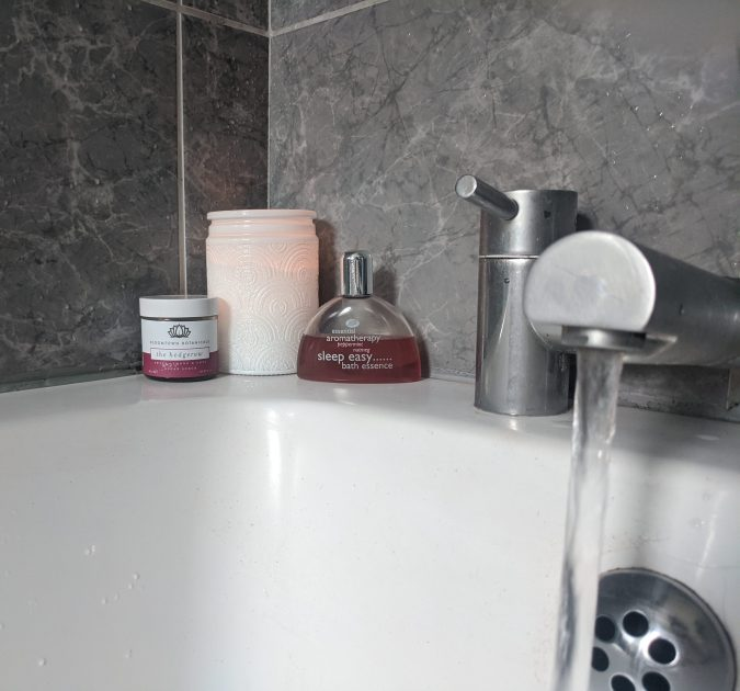 Bathroom with white bath and grey marble tiles, white candle and bath products