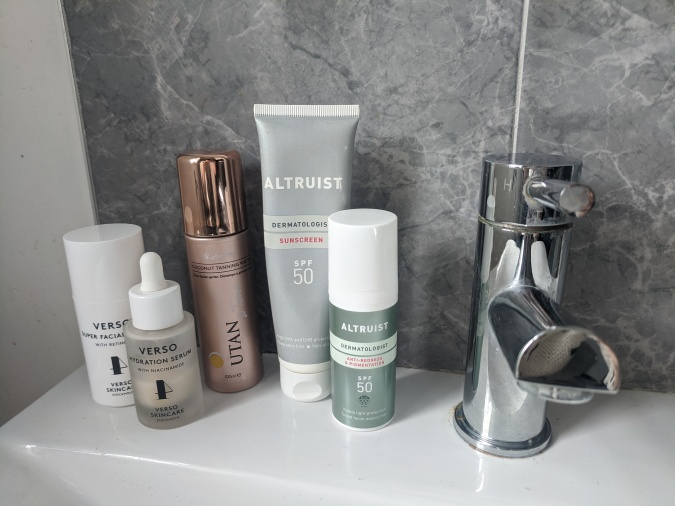 Pandemic Pampering How To Lockdown Your Winning Morning Routine by Fashion Du Jour LDN. Grey marble bathroom tiles with silver tap and white sink,various skincare products by Verso, U-Tan and Altruist Suncare