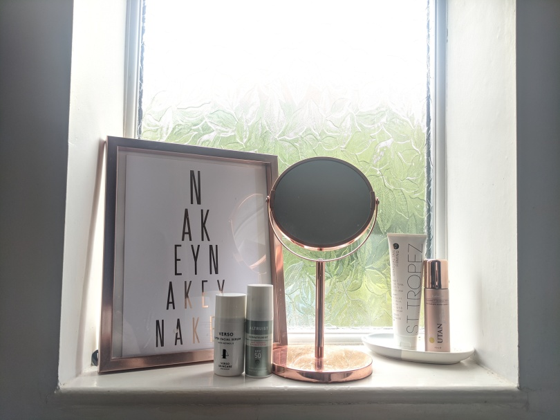 "Pandemic Pampering How To Lockdown Your Winning Morning Routine by Fashion Du Jour LDN. Bathroom, Rose gold mirror, rose gold frame with ""Nakey Nakey Nakey""quote, beauty products"