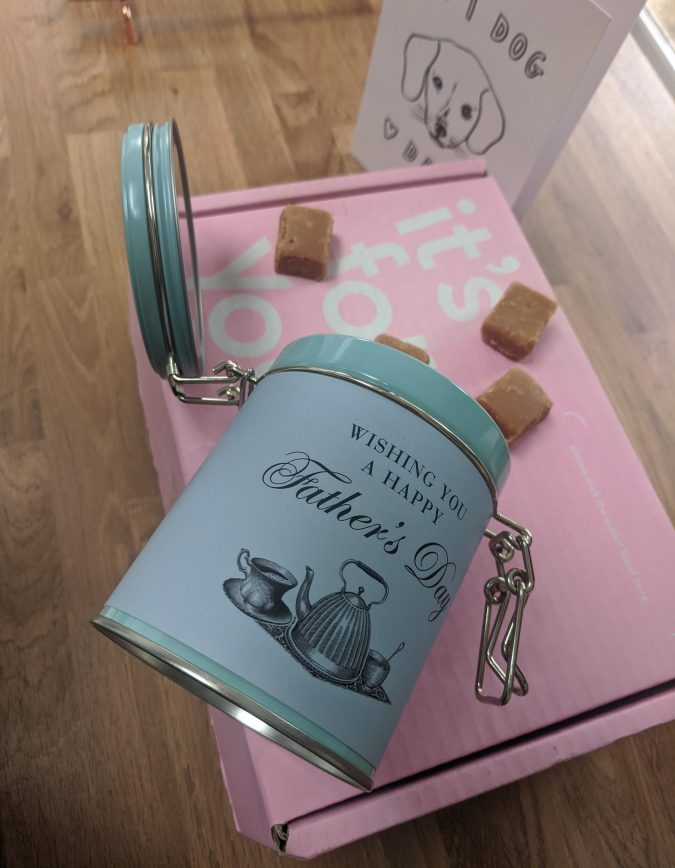 Father's Day 2020 How To Celebrate, Whether Near Or Far. Pink Moonpig Cardboard box, white father's day card with dog on it, blue tin of fudge with Happy Father's Day, with Salted Caramel Fudge spilling out