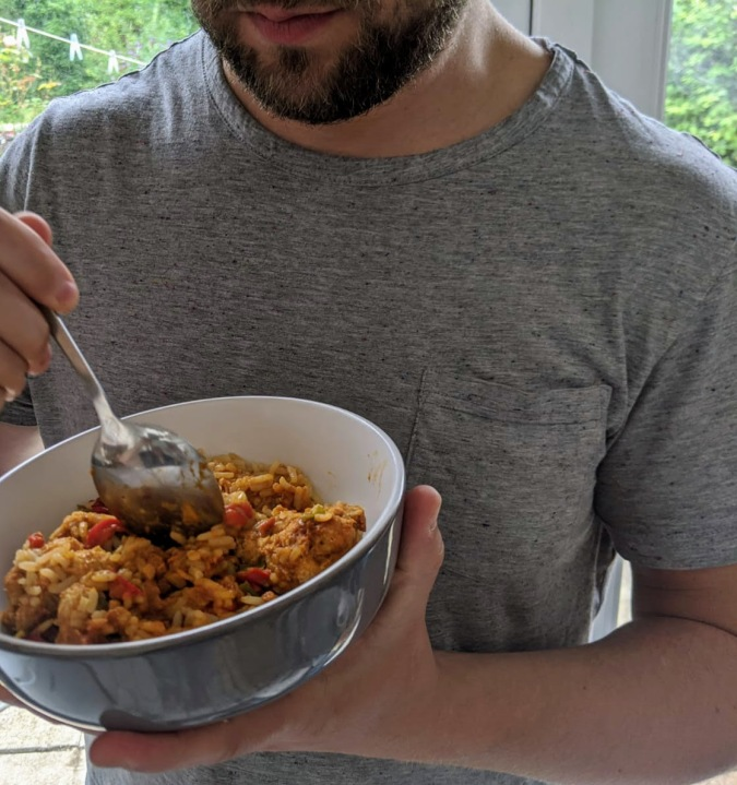 Small Prices Big Gains How Musclefood Can Transform Your Meal Time And You By Fashion Du Jour LDN. Bearded muscly man in a grey t-shirt eating Musclefood Prepped Pots Moroccan Pork Meatballs and Cous Cous