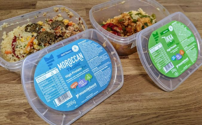 Small Prices Big Gains How Musclefood Can Transform Your Meal Time And You By Fashion Du Jour LDN. Muscle Food Prep Pots Moroccan Pork Meatballs and Cous Cous and Meatfree Mock Chicken Tikka on wooden kitchen worktop